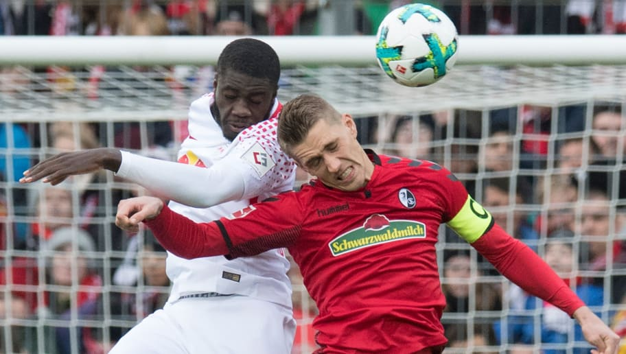 Freiburg's German forward Nils Petersen (R) and Leipzig's French defender Dayot Upamecano vie for the ball during the German first division Bundesliga football match SC Freiburg vs RB Leipzig in Freiburg, southwestern Germany, on January 20, 2018. / AFP PHOTO / THOMAS KIENZLE / RESTRICTIONS: DURING MATCH TIME: DFL RULES TO LIMIT THE ONLINE USAGE TO 15 PICTURES PER MATCH AND FORBID IMAGE SEQUENCES TO SIMULATE VIDEO. == RESTRICTED TO EDITORIAL USE == FOR FURTHER QUERIES PLEASE CONTACT DFL DIRECTLY AT + 49 69 650050         (Photo credit should read THOMAS KIENZLE/AFP/Getty Images)