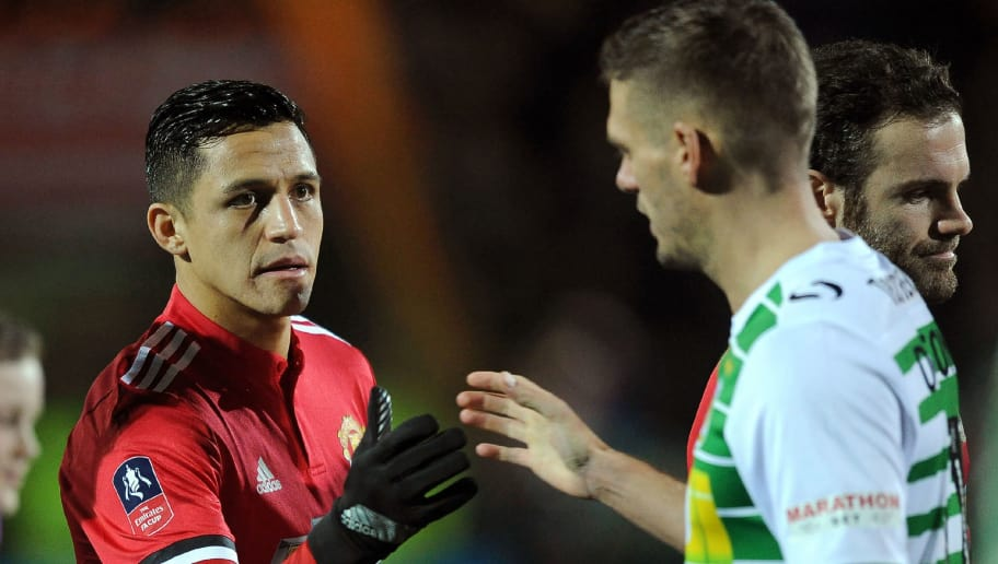Manchester United's Chilean striker Alexis Sanchez (L) shakes hands with Yeovil Town's players ahead of the FA Cup fourth round football match between Yeovil Town and Manchester United at Huish Park in Yeovil, Somerset on January 26, 2018. / AFP PHOTO / - / RESTRICTED TO EDITORIAL USE. No use with unauthorized audio, video, data, fixture lists, club/league logos or 'live' services. Online in-match use limited to 75 images, no video emulation. No use in betting, games or single club/league/player publications.  /         (Photo credit should read -/AFP/Getty Images)