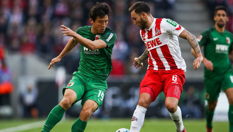 COLOGNE, GERMANY - JANUARY 27: Koo Ja-Cheol #19 of Augsburg and Marco Hoger #6 of 1.FC Koeln battle for the ball during the Bundesliga match between 1. FC Koeln and FC Augsburg at RheinEnergieStadion on January 27, 2018 in Cologne, Germany. (Photo by Maja Hitij/Bongarts/Getty Images)