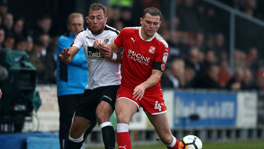 DARTFORD, ENGLAND - NOVEMBER 05:  Ryan Hayes of Dartford tackles Matty Preston of Swindon Town during The Emirates FA Cup first round match between Dartford and Swindon Town at the Princes Park Stadium on November 5, 2017 in Dartford, England.  (Photo by Bryn Lennon/Getty Images)