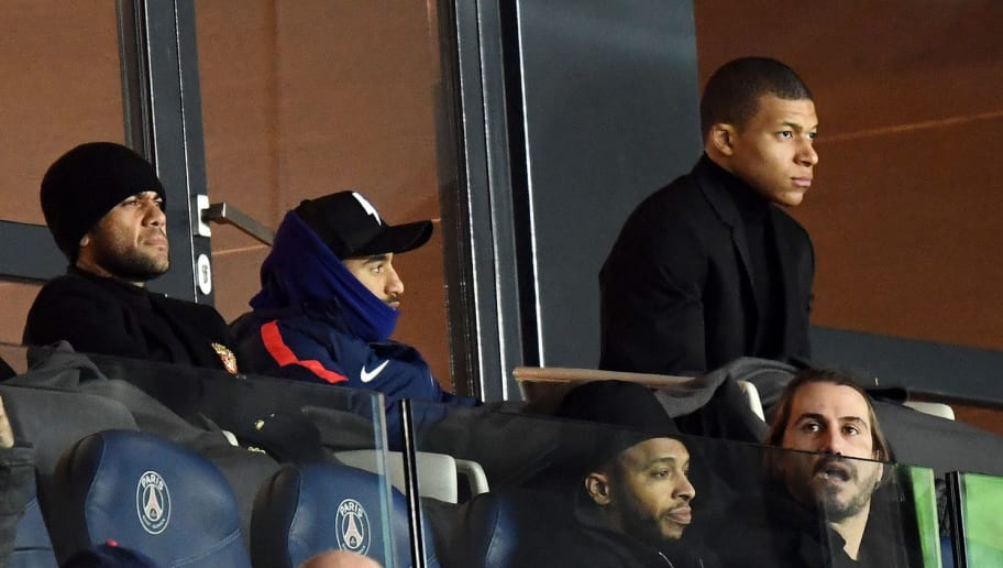 (L-R) Paris Saint-Germain's Brazilian defender Dani Alves, Paris Saint-Germain's Brazilian midfielder Lucas Moura and Paris Saint-Germain's French forward Kylian MBappe sit in the tribunes as they attend during the French L1 football match between Paris Saint-Germain (PSG) and Montpellier (MHSC) at the Parc des Princes stadium in Paris on January 27, 2018. / AFP PHOTO / FRANCK FIFE        (Photo credit should read FRANCK FIFE/AFP/Getty Images)