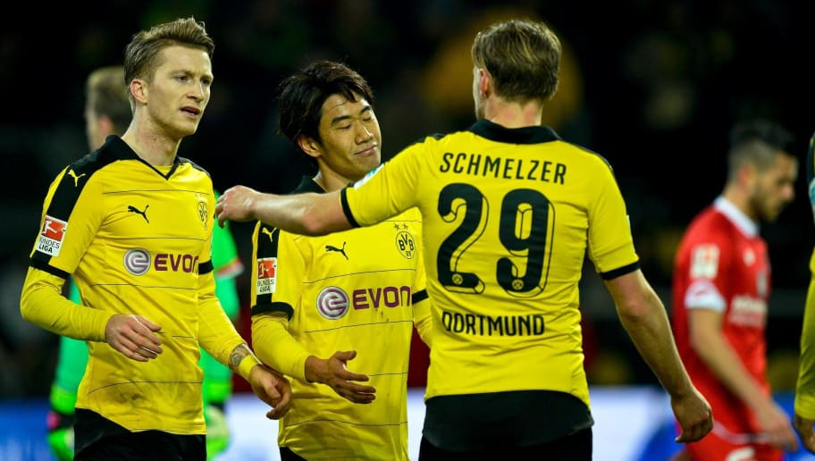 Dortmund's Japanese midfielder Shinji Kagawa (C) celebrates scoring the 2-0 goal with his team-mates Marco Reus (L) and Marcel Schmelzer during the German first division Bundesliga football match Borussia Dortmund v 1 FSV Mainz 05 in Dortmund, on March 13, 2016. / AFP / Sascha SCHUERMANN / RESTRICTIONS: DURING MATCH TIME: DFL RULES TO LIMIT THE ONLINE USAGE TO 15 PICTURES PER MATCH AND FORBID IMAGE SEQUENCES TO SIMULATE VIDEO. == RESTRICTED TO EDITORIAL USE == FOR FURTHER QUERIES PLEASE CONTACT DFL DIRECTLY AT + 49 69 650050         (Photo credit should read SASCHA SCHUERMANN/AFP/Getty Images)