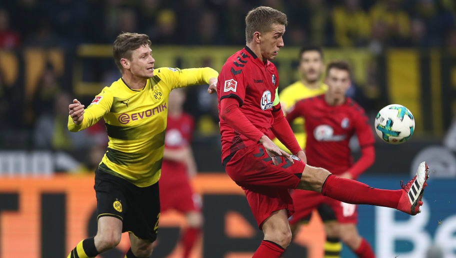 DORTMUND, GERMANY - JANUARY 27: Nils Petersen of Freiburg (r) tries to control the ball as Lukasz Piszczek of Dortmund looks on during the Bundesliga match between Borussia Dortmund and Sport-Club Freiburg at Signal Iduna Park on January 27, 2018 in Dortmund, Germany. (Photo by Lars Baron/Bongarts/Getty Images)