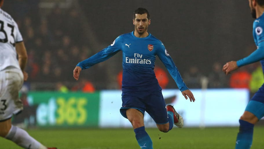 Arsenal's Armenian midfielder Henrikh Mkhitaryan runs with the ball during the English Premier League football match between Swansea City and Arsenal at The Liberty Stadium in Swansea, south Wales on January 30, 2018. / AFP PHOTO / Geoff CADDICK / RESTRICTED TO EDITORIAL USE. No use with unauthorized audio, video, data, fixture lists, club/league logos or 'live' services. Online in-match use limited to 75 images, no video emulation. No use in betting, games or single club/league/player publications.  /         (Photo credit should read GEOFF CADDICK/AFP/Getty Images)