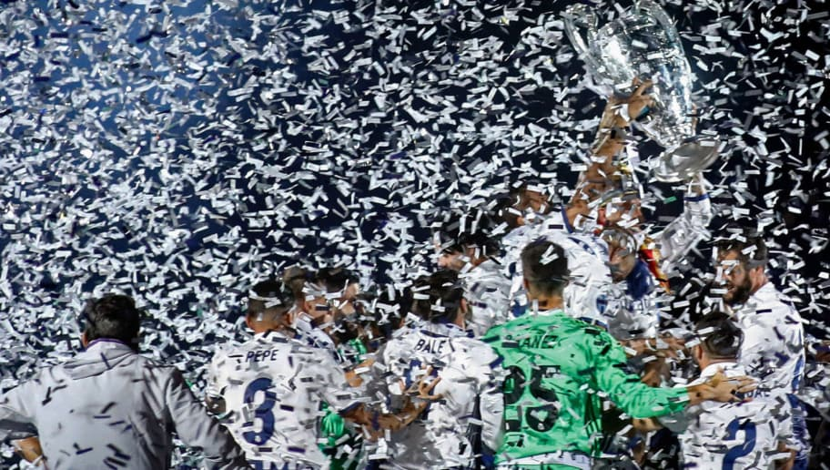 Real Madrid players hold up the trophy as they celebrate the team's win at the Santiago Bernabeu stadium in Madrid on June 4, 2017 after winning the UEFA Champions League football match final Juventus vs Real Madrid CF held at the National Stadium of Wales in Cardiff on June 3, 2017. / AFP PHOTO / OSCAR DEL POZO        (Photo credit should read OSCAR DEL POZO/AFP/Getty Images)
