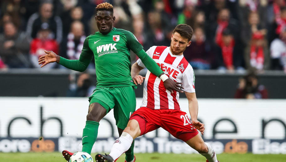 COLOGNE, GERMANY - JANUARY 27: Salih Oezcan #20 of 1.FC Koeln and Daniel Opare #4 of Augsburg battle for the ball during the Bundesliga match between 1. FC Koeln and FC Augsburg at RheinEnergieStadion on January 27, 2018 in Cologne, Germany. (Photo by Maja Hitij/Bongarts/Getty Images)