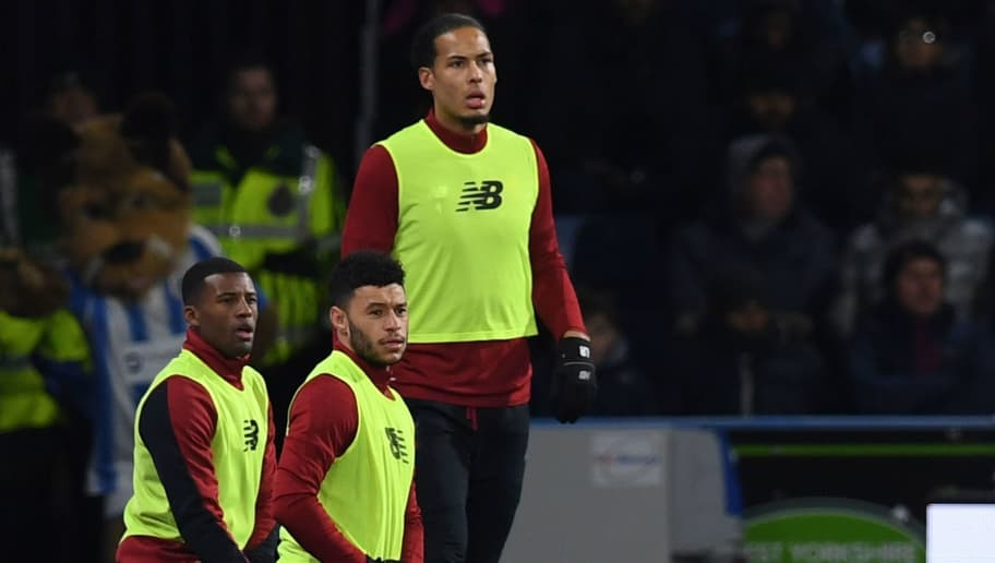 Liverpool's Dutch midfielder Georginio Wijnaldum (L), Liverpool's English midfielder Alex Oxlade-Chamberlain (C) and Liverpool's Dutch defender Virgil van Dijk (R) warm up on the touchline during the English Premier League football match between Huddersfield Town and Liverpool at the John Smith's stadium in Huddersfield, northern England on January 30, 2018. / AFP PHOTO / Paul ELLIS / RESTRICTED TO EDITORIAL USE. No use with unauthorized audio, video, data, fixture lists, club/league logos or 'live' services. Online in-match use limited to 75 images, no video emulation. No use in betting, games or single club/league/player publications.  /         (Photo credit should read PAUL ELLIS/AFP/Getty Images)