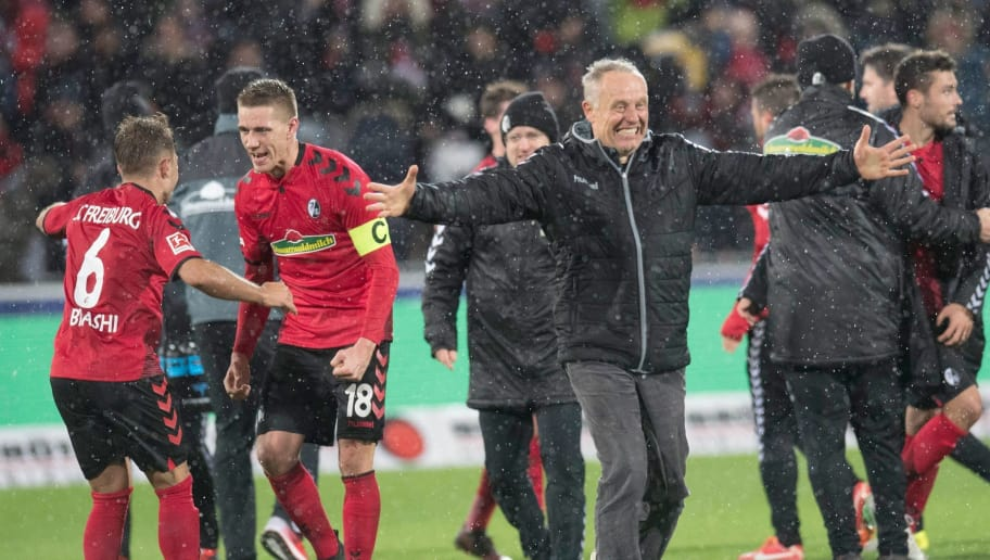 (L-R) Freiburg's Albanian midfielder Amir Abrashi, Freiburg's German forward Nils Petersen and Freiburg's German head coach Christian Streich celebrate after winning the German first division Bundesliga football match SC Freiburg vs RB Leipzig in Freiburg, southwestern Germany, on January 20, 2018. / AFP PHOTO / THOMAS KIENZLE / RESTRICTIONS: DURING MATCH TIME: DFL RULES TO LIMIT THE ONLINE USAGE TO 15 PICTURES PER MATCH AND FORBID IMAGE SEQUENCES TO SIMULATE VIDEO. == RESTRICTED TO EDITORIAL USE == FOR FURTHER QUERIES PLEASE CONTACT DFL DIRECTLY AT + 49 69 650050         (Photo credit should read THOMAS KIENZLE/AFP/Getty Images)
