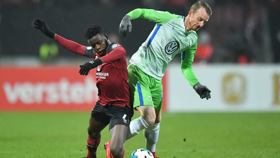 NUREMBERG, GERMANY - DECEMBER 19: Edgar Salli of Nuernberg and Maximilian Arnold of Wolfsburg compete for the ball during the DFB Cup match between 1. FC Nuernberg and VfL Wolfsburg at Max-Morlock-Stadion on December 19, 2017 in Nuremberg, Germany. (Photo by Sebastian Widmann/Bongarts/Getty Images)