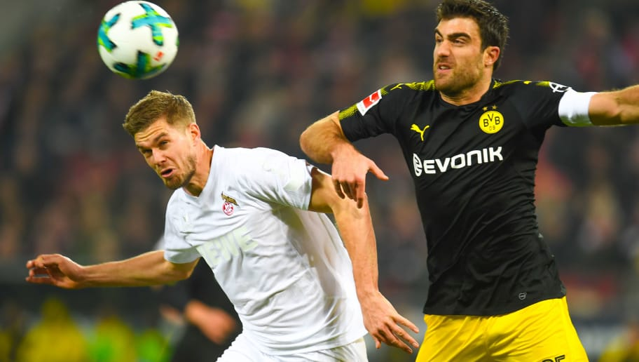 Cologne's Simon Terrode and Dortmund's Greek defender Sokratis vie for the ball during the German first division Bundesliga football match FC Cologne vs Borussia Dortmund in Cologne, western Germany, on February 2, 2018. / AFP PHOTO / Patrik STOLLARZ / RESTRICTIONS: DURING MATCH TIME: DFL RULES TO LIMIT THE ONLINE USAGE TO 15 PICTURES PER MATCH AND FORBID IMAGE SEQUENCES TO SIMULATE VIDEO. == RESTRICTED TO EDITORIAL USE == FOR FURTHER QUERIES PLEASE CONTACT DFL DIRECTLY AT + 49 69 650050         (Photo credit should read PATRIK STOLLARZ/AFP/Getty Images)