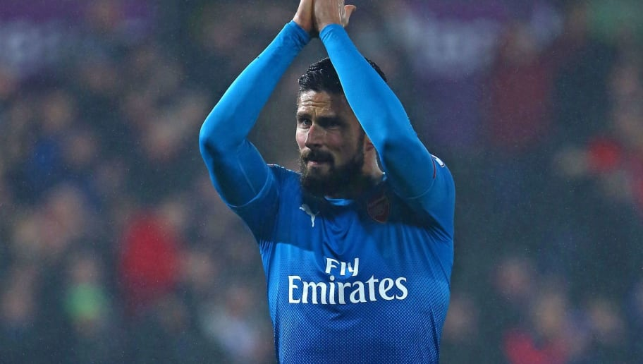 Arsenal's French striker Olivier Giroud applauds supporters on the pitch after the English Premier League football match between Swansea City and Arsenal at The Liberty Stadium in Swansea, south Wales on January 30, 2018. Swansea won the game 3-1. / AFP PHOTO / Geoff CADDICK / RESTRICTED TO EDITORIAL USE. No use with unauthorized audio, video, data, fixture lists, club/league logos or 'live' services. Online in-match use limited to 75 images, no video emulation. No use in betting, games or single club/league/player publications.  /         (Photo credit should read GEOFF CADDICK/AFP/Getty Images)