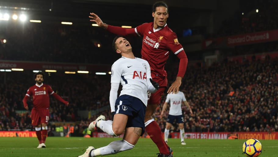 Tottenham Hotspur's Argentinian midfielder Erik Lamela (L) goes down from a tackle by Liverpool's Dutch defender Virgil van Dijk (R), leading to the second penalty and goal by Tottenham Hotspur's English striker Harry Kane during the English Premier League football match between Liverpool and Tottenham Hotspur at Anfield in Liverpool, north west England on February 4, 2018. / AFP PHOTO / PAUL ELLIS / RESTRICTED TO EDITORIAL USE. No use with unauthorized audio, video, data, fixture lists, club/league logos or 'live' services. Online in-match use limited to 75 images, no video emulation. No use in betting, games or single club/league/player publications.  /         (Photo credit should read PAUL ELLIS/AFP/Getty Images)