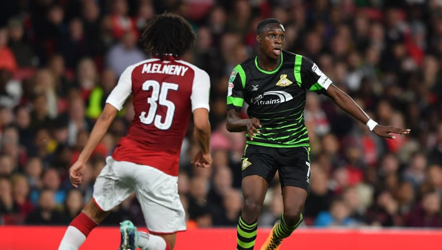Doncaster Rovers' Dutch midfielder Rodney Kongolo (R) vies with Arsenal's Egyptian midfielder Mohamed Elneny during the English League Cup third round football match between Arsenal and Doncaster Rovers at The Emirates Stadium in London on September 20, 2017. / AFP PHOTO / Ben STANSALL / RESTRICTED TO EDITORIAL USE. No use with unauthorized audio, video, data, fixture lists, club/league logos or 'live' services. Online in-match use limited to 75 images, no video emulation. No use in betting, games or single club/league/player publications.  /         (Photo credit should read BEN STANSALL/AFP/Getty Images)