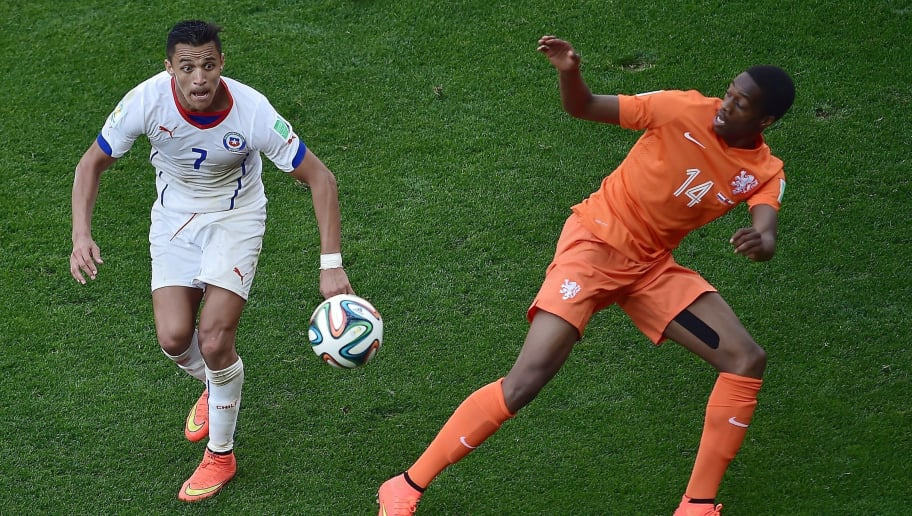 Chile's forward Alexis Sanchez (L) vies with Netherlands' defender Terence Kongolo during a Group B football match between Netherlands and Chile at the Corinthians Arena in Sao Paulo during the 2014 FIFA World Cup on June 23, 2014. Netherlands won 2-0.     AFP PHOTO/ GABRIEL BOUYS        (Photo credit should read GABRIEL BOUYS/AFP/Getty Images)