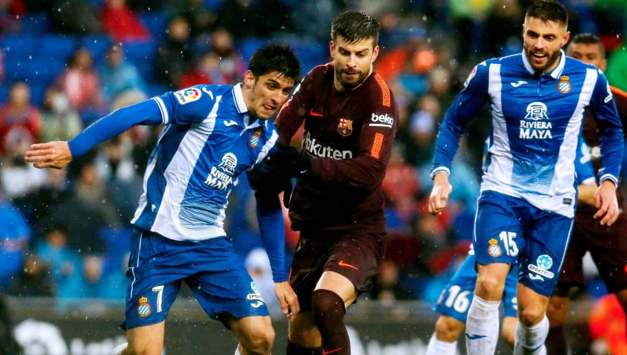 Barcelona's Spanish defender Gerard Pique (C) vies with Espanyol's Spanish forward Gerard Moreno (L) during the Spanish league football match between RCD Espanyol and FC Barcelona at the RCDE Stadium in Cornella de Llobregat on February 4, 2018. / AFP PHOTO / PAU BARRENA        (Photo credit should read PAU BARRENA/AFP/Getty Images)