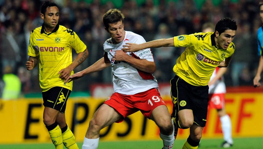 OFFENBACH, GERMANY - OCTOBER 27:  Nicolas Feldhahn (L) of Offenbach battles for the ball with Nuri Sahin (R) of Dortmund during the DFB Cup second round match between Kickers Offenbach and Borussia Dortmund at Bieberer Berg stadium on October 27, 2010 in Offenbach, Germany.  (Photo by Thorsten Wagner/Bongarts/Getty Images)