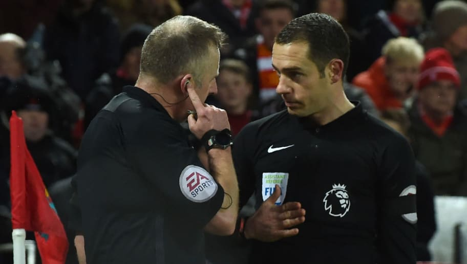 Referee Johnathan Moss (L) discusses the first penalty with the linesman  during the English Premier League football match between Liverpool and Tottenham Hotspur at Anfield in Liverpool, north west England on February 4, 2018. / AFP PHOTO / PAUL ELLIS / RESTRICTED TO EDITORIAL USE. No use with unauthorized audio, video, data, fixture lists, club/league logos or 'live' services. Online in-match use limited to 75 images, no video emulation. No use in betting, games or single club/league/player publications.  /         (Photo credit should read PAUL ELLIS/AFP/Getty Images)