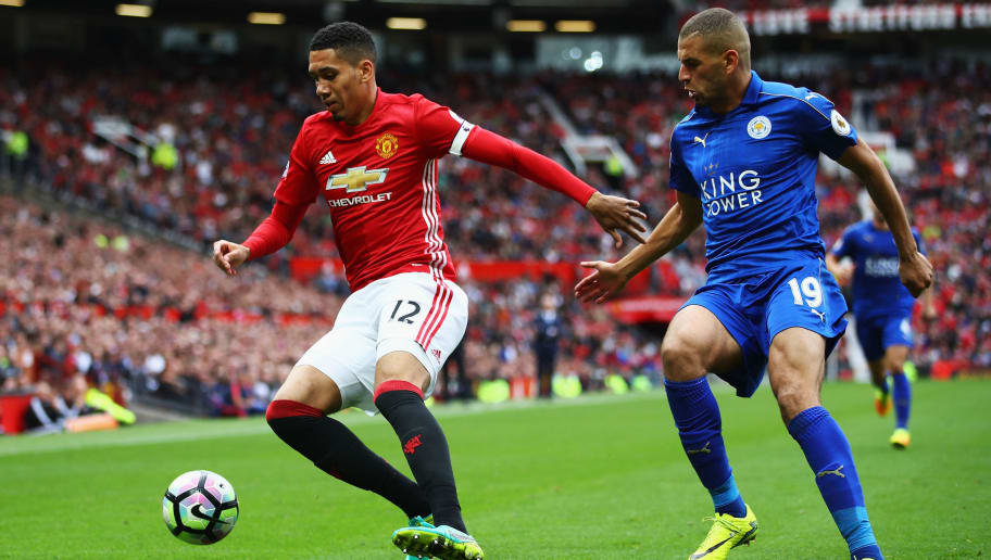 MANCHESTER, ENGLAND - SEPTEMBER 24: Chris Smalling of Manchester United (L) attempts to keep the ball while under pressure from Islam Slimani of Leicester City (R)  during the Premier League match between Manchester United and Leicester City at Old Trafford on September 24, 2016 in Manchester, England.  (Photo by Clive Brunskill/Getty Images)
