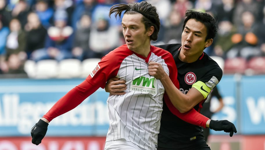 Augsburg's Austrian forward Michael Gregoritsch and Frankfurt's Japanese midfielder Makoto Hasebe vie for the ball during the German first division Bundesliga football match 1 FC Augsburg vs Eintracht Frankfurt in Augsburg, southern Germany, on February 4, 2018. / AFP PHOTO / Guenter SCHIFFMANN / RESTRICTIONS: DURING MATCH TIME: DFL RULES TO LIMIT THE ONLINE USAGE TO 15 PICTURES PER MATCH AND FORBID IMAGE SEQUENCES TO SIMULATE VIDEO. == RESTRICTED TO EDITORIAL USE == FOR FURTHER QUERIES PLEASE CONTACT DFL DIRECTLY AT + 49 69 650050         (Photo credit should read GUENTER SCHIFFMANN/AFP/Getty Images)
