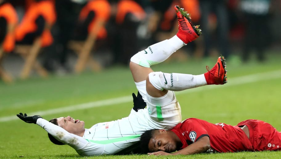 LEVERKUSEN, GERMANY - FEBRUARY 06: Milot Rashica of Bremen (L) falls over Wendell of Leverkusen (R) during the DFB Cup quarter final match between Bayer Leverkusen and Werder Bermen at BayArena on February 6, 2018 in Leverkusen, Germany. (Photo by Christof Koepsel/Bongarts/Getty Images)