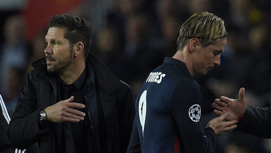 Atletico Madrid's forward Fernando Torres (R) passes by Atletico Madrid's Argentinian coach Diego Simeone as he leaves the pitch after being sent off by referee during the UEFA Champions League quarter finals first leg football match FC Barcelona vs Atletico de Madrid at the Camp Nou stadium in Barcelona on April 5, 2016. / AFP / LLUIS GENE        (Photo credit should read LLUIS GENE/AFP/Getty Images)