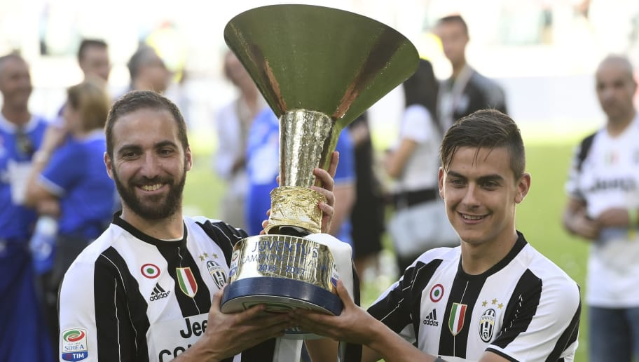 Juventus' forward from Argentina Paulo Dybala (R) and Juventus' forward from Argentina Gonzalo Higuain pose with the trophy after winning the Italian Serie A football match Juventus vs Crotone and the 'Scudetto' at the Juventus Stadium in Turin on May 21, 2017. First-half goals from Mario Mandzukic and Paulo Dybala, and a late header from Alex Sandro sealed a 3-0 win over Crotone to hand Juventus a record sixth consecutive Serie A title today. / AFP PHOTO / MIGUEL MEDINA        (Photo credit should read MIGUEL MEDINA/AFP/Getty Images)