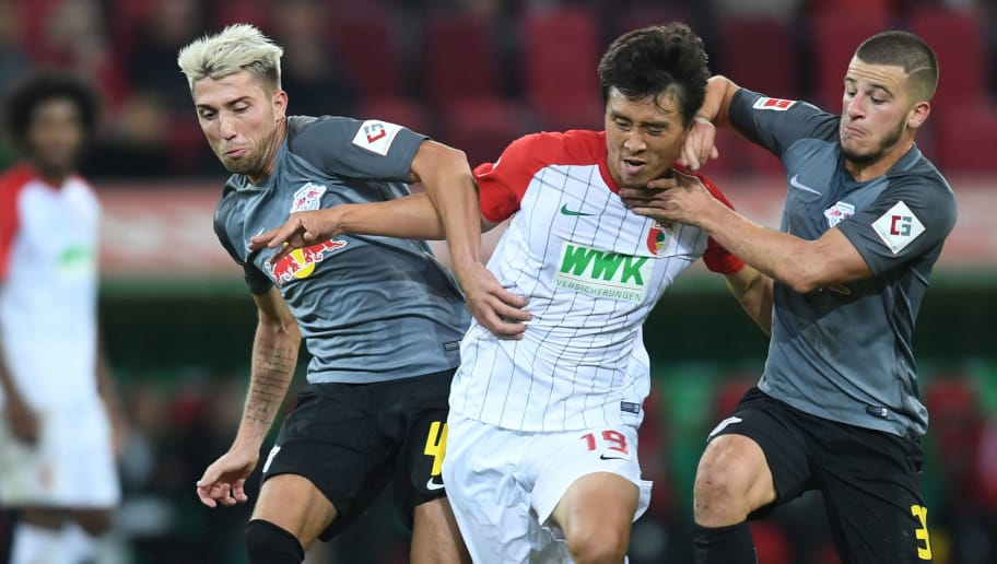 (L-R) Leipzig's Slovanian midfielder Kevin Kampl, Augsburg's South Korean midfielder Koo Ja-cheol and Leipzig's Swedish midfielder Emil Forsberg vie for the ball during the German First division Bundesliga football match between FC Augsburg and RB Leipzig in Augsburg, southern Germany, on September 19, 2017. / AFP PHOTO / Christof STACHE / RESTRICTIONS: DURING MATCH TIME: DFL RULES TO LIMIT THE ONLINE USAGE TO 15 PICTURES PER MATCH AND FORBID IMAGE SEQUENCES TO SIMULATE VIDEO. == RESTRICTED TO EDITORIAL USE == FOR FURTHER QUERIES PLEASE CONTACT DFL DIRECTLY AT + 49 69 650050         (Photo credit should read CHRISTOF STACHE/AFP/Getty Images)