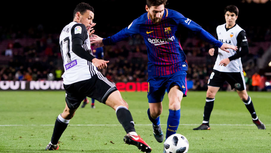 BARCELONA, SPAIN - FEBRUARY 01: Lionel Messi of FC Barcelona dribbles Francis Coquelin of Valencia CF to assist his teammate Luis Suarez to score the opening goal during the Copa del Rey semi-final first leg match between FC Barcelona and Valencia CF at Camp Nou on February 1, 2018 in Barcelona, Spain. (Photo by Alex Caparros/Getty Images)