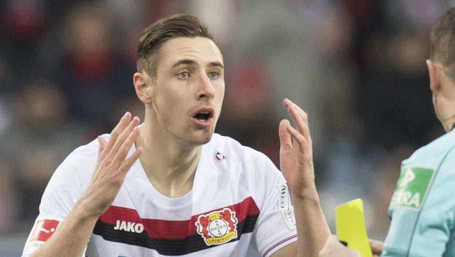 Leverkusen's  midfielder Dominik Kohr reacts as referee Robert Kampka shows the yellow card during the German first division Bundesliga football match SC Freiburg versus Bayer Leverkusen on February 3, 2018 in Freiburg. / AFP PHOTO / THOMAS KIENZLE / RESTRICTIONS: DURING MATCH TIME: DFL RULES TO LIMIT THE ONLINE USAGE TO 15 PICTURES PER MATCH AND FORBID IMAGE SEQUENCES TO SIMULATE VIDEO. == RESTRICTED TO EDITORIAL USE == FOR FURTHER QUERIES PLEASE CONTACT DFL DIRECTLY AT + 49 69 650050         (Photo credit should read THOMAS KIENZLE/AFP/Getty Images)