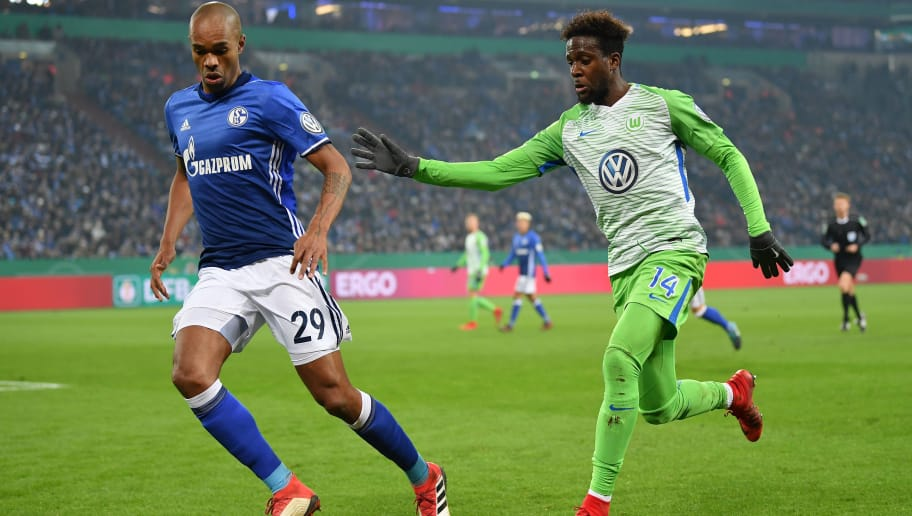 GELSENKIRCHEN, GERMANY - FEBRUARY 07:  Divock Origi of Wolfsburg is challenged by Naldo of Schalke during the DFB Pokal quarter final match between FC Schalke 04 and VfL Wolfsburg at Veltins-Arena on February 7, 2018 in Gelsenkirchen, Germany.  (Photo by Stuart Franklin/Bongarts/Getty Images)