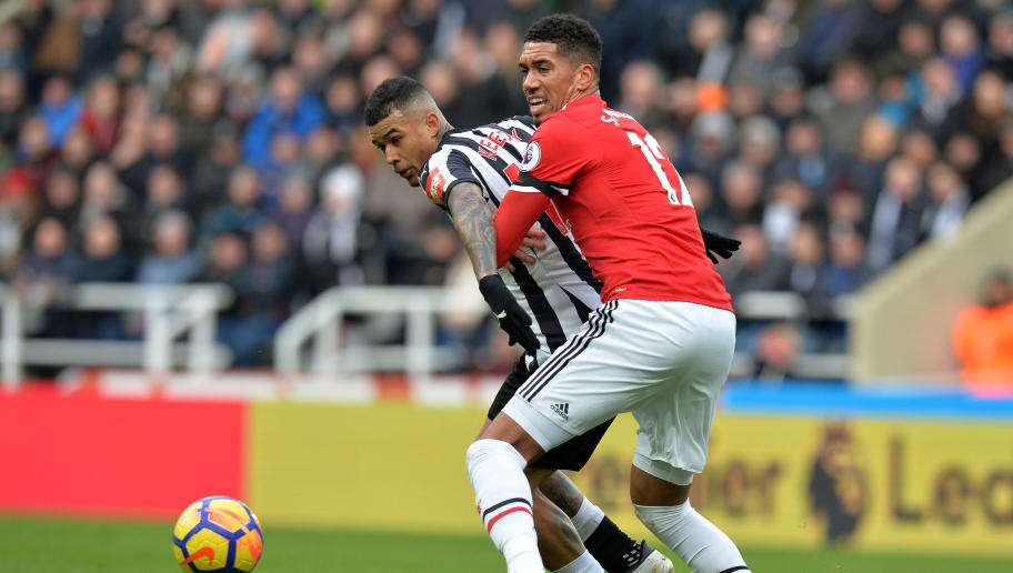 NEWCASTLE UPON TYNE, ENGLAND - FEBRUARY 11:  Kenedy of Newcastle United is challenged by Chris Smalling of Manchester United during the Premier League match between Newcastle United and Manchester United at St. James Park on February 11, 2018 in Newcastle upon Tyne, England.  (Photo by Mark Runnacles/Getty Images)