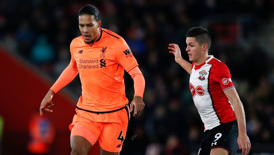 Liverpool's Dutch defender Virgil van Dijk (L) is challenged by Southampton's Argentinian striker Guido Carrillo (R) during the English Premier League football match between Southampton and Liverpool at St Mary's Stadium in Southampton, southern England on February 11, 2018. / AFP PHOTO / Adrian DENNIS / RESTRICTED TO EDITORIAL USE. No use with unauthorized audio, video, data, fixture lists, club/league logos or 'live' services. Online in-match use limited to 75 images, no video emulation. No use in betting, games or single club/league/player publications.  /         (Photo credit should read ADRIAN DENNIS/AFP/Getty Images)