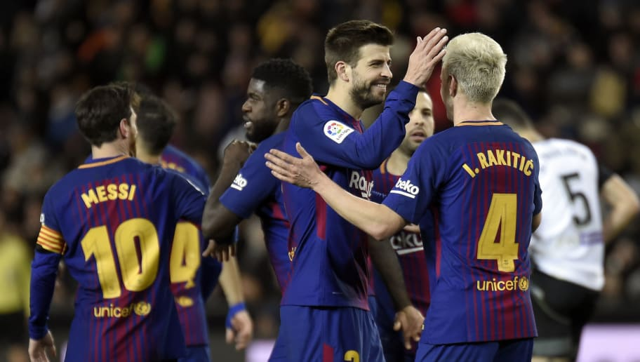 Barcelona's Spanish defender Gerard Pique (2R) congratulates Barcelona's Croatian midfielder Ivan Rakitic after scoring their team's second goal during the Spanish 'Copa del Rey' (King's cup) second leg semi-final football match between Valencia CF and FC Barcelona at the Mestalla stadium in Valencia on February 8, 2018. / AFP PHOTO / JOSE JORDAN        (Photo credit should read JOSE JORDAN/AFP/Getty Images)