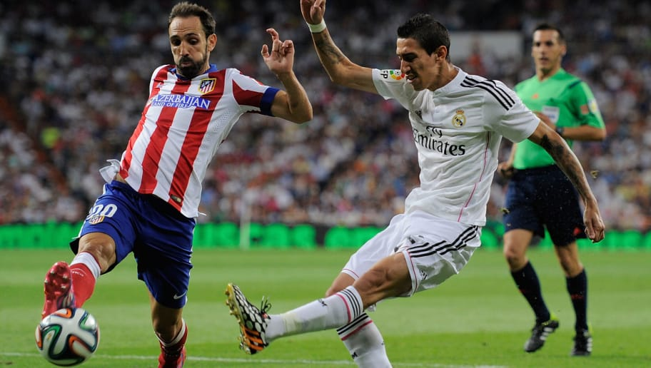 MADRID, SPAIN - AUGUST 19:  Angel di Maria (R) of Real Madrid shoots past Raul Garcia of Club Atletico de Madrid during the Supercopa first leg match between Real Madrid and Club Atletico de Madrid at Estadio Santiago Bernabeu on August 19, 2014 in Madrid, Spain.  (Photo by Denis Doyle/Getty Images)