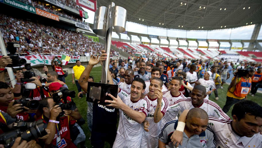 Fluminense's Fred (C) holds the Brazilian Football Championship trophy as he celebrates with teammates on November 18, 2012 at the Joao Havelange stadium in Rio de Janeiro, Brazil.  AFP  PHOTO /  ANTONIO SCORZA        (Photo credit should read ANTONIO SCORZA/AFP/Getty Images)