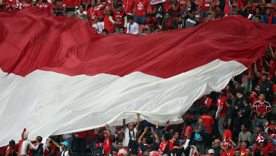 Indonesian fans wave a giant flag before the AFF Suzuki Cup group B football match between Malaysia and Indonesia in Bukit Jalil Stadium outside Kuala Lumpur on December 1, 2012. AFP PHOTO / MOHD RASFAN        (Photo credit should read MOHD RASFAN/AFP/Getty Images)