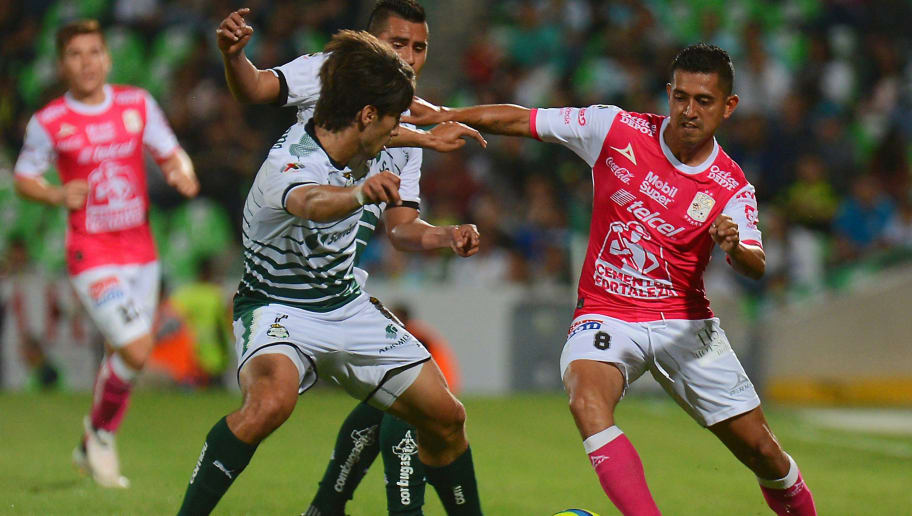 Jose Abella (L) of Santos vies for the ball with Luis Montes (R) of Leon during their Mexican Clausura tournament football match at the TSM Corona stadium on February 14, 2018 in Torreon, Mexico. / AFP PHOTO / OSCAR WONG        (Photo credit should read OSCAR WONG/AFP/Getty Images)