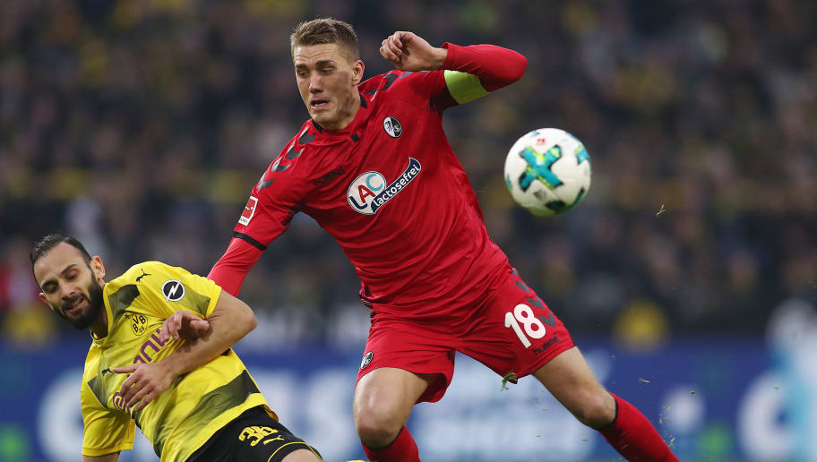 DORTMUND, GERMANY - JANUARY 27: Nils Petersen of Freiburg (r) fights for the ball with Oemer Toprak of Dortmund during the Bundesliga match between Borussia Dortmund and Sport-Club Freiburg at Signal Iduna Park on January 27, 2018 in Dortmund, Germany. (Photo by Lars Baron/Bongarts/Getty Images)