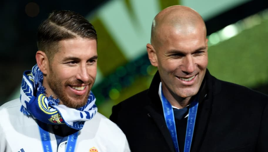 Real Madrid's captain and defender Sergio Ramos (L) holding a championship trophy poses with head coach Zinedine Zidane (R) after they won the Club World Cup football final match between Kashima Antlers of Japan and Real Madrid of Spain at Yokohama International stadium in Yokohama on December 18, 2016. / AFP / TOSHIFUMI KITAMURA        (Photo credit should read TOSHIFUMI KITAMURA/AFP/Getty Images)