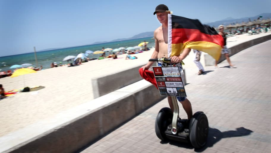 A German tourist waves a German flag while riding a segway at Palma's Beach in Palma de Mallorca on July 6, 2010, on the eve of the World Cup semi-final football match Spain against Germany. AFP PHOTO Jaime REINA (Photo credit should read JAIME REINA/AFP/Getty Images)