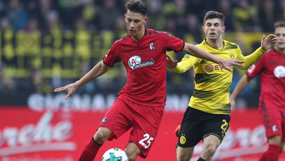 DORTMUND, GERMANY - JANUARY 27: Robin Koch of Freiburg (l) runs with the ball past Christian Pulisic of Dortmund during the Bundesliga match between Borussia Dortmund and Sport-Club Freiburg at Signal Iduna Park on January 27, 2018 in Dortmund, Germany. (Photo by Lars Baron/Bongarts/Getty Images)