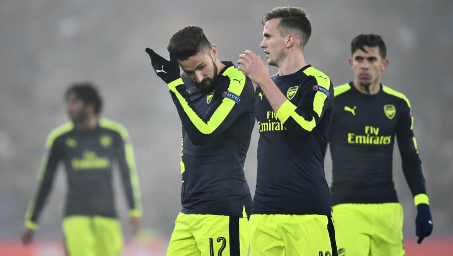 Arsenal's French forward Olivier Giroud (L) and Arsenal's English defender Rob Holding (2ndR) react at the end of the UEFA Champions league Group A football match between FC Basel 1893 and Arsenal FC on December 6, 2016 at the St Jakob Park stadium in Basel. / AFP / Fabrice COFFRINI        (Photo credit should read FABRICE COFFRINI/AFP/Getty Images)