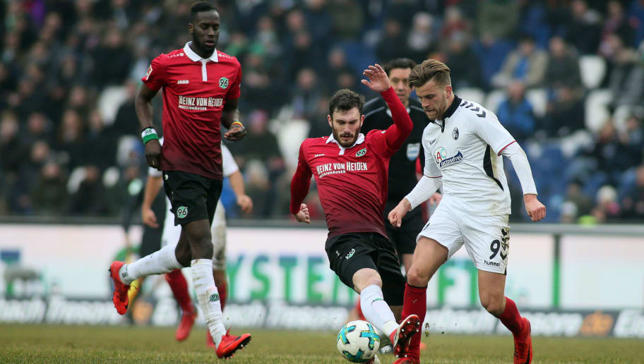 HANOVER, GERMANY - FEBRUARY 10: Josip Elez of Hannover 96 (M) fights for the ball with Lucas Hoeler of SC Freiburg (R) during the Bundesliga match between Hannover 96 and Sport-Club Freiburg at HDI-Arena on February 10, 2018 in Hanover, Germany. (Photo by Selim Sudheimer/Bongarts/Getty Images)