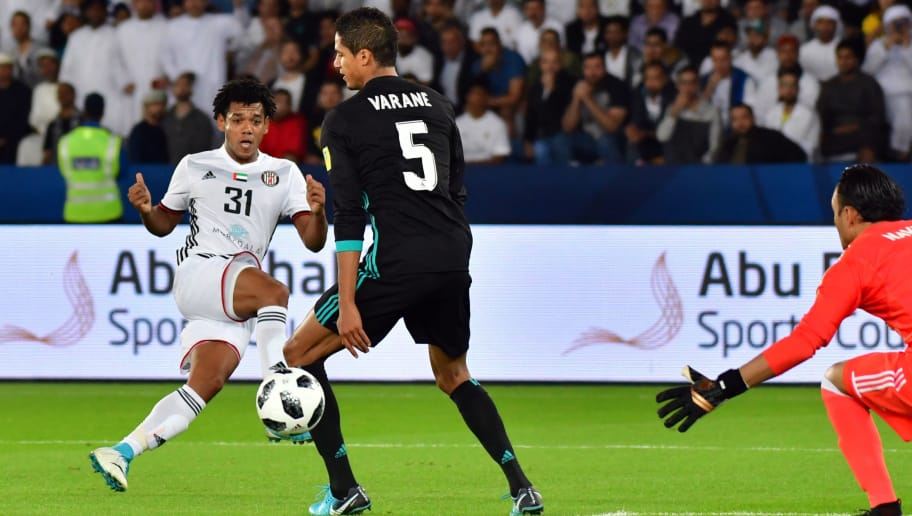 Al-Jazira's Brazilian forward Romarinho (L) bends a shot around Real Madrid's French defender Raphael Varane (C) and Costa Rican goalkeeper Keylor Navas (R) during the FIFA Club World Cup semi-final match in the Emirati capital Abu Dhabi on December 13, 2017. Romarinho opened the scoring for his side before the end of the first half. / AFP PHOTO / GIUSEPPE CACACE        (Photo credit should read GIUSEPPE CACACE/AFP/Getty Images)