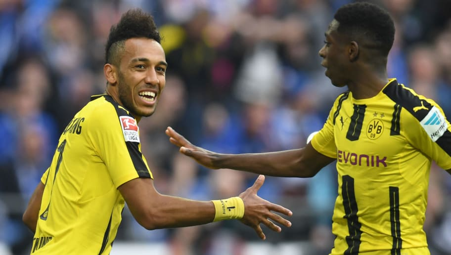 Dortmund's Gabonese striker Pierre-Emerick Aubameyang (L) celebrates with his teammate French midfielder Ousmane Dembele after scoring the 0-1 during the German first division Bundesliga football match between FC Schalke 04 and Borussia Dortmund in Gelsenkirchen, western Germany, on April 1, 2017. / AFP PHOTO / PATRIK STOLLARZ / RESTRICTIONS: DURING MATCH TIME: DFL RULES TO LIMIT THE ONLINE USAGE TO 15 PICTURES PER MATCH AND FORBID IMAGE SEQUENCES TO SIMULATE VIDEO. == RESTRICTED TO EDITORIAL USE == FOR FURTHER QUERIES PLEASE CONTACT DFL DIRECTLY AT + 49 69 650050         (Photo credit should read PATRIK STOLLARZ/AFP/Getty Images)