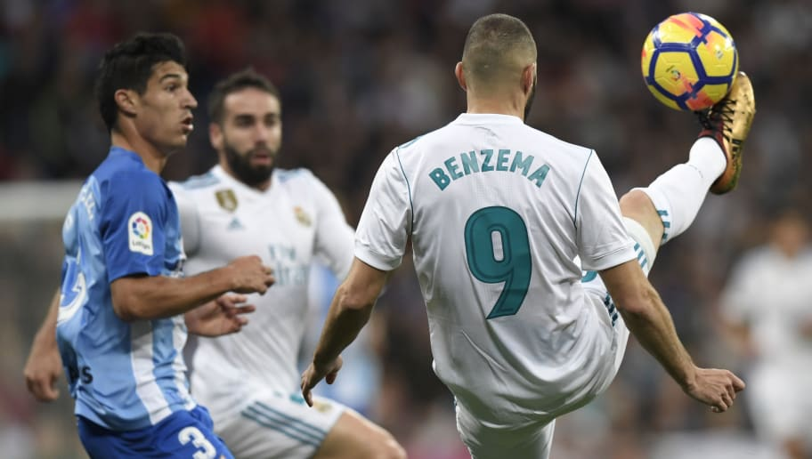 Real Madrid's French forward Karim Benzema (R) controls the ball during the Spanish league football match Real Madrid CF against Malaga CF on 25, November 2017 at the Santiago Bernabeu stadium in Madrid. / AFP PHOTO / GABRIEL BOUYS        (Photo credit should read GABRIEL BOUYS/AFP/Getty Images)