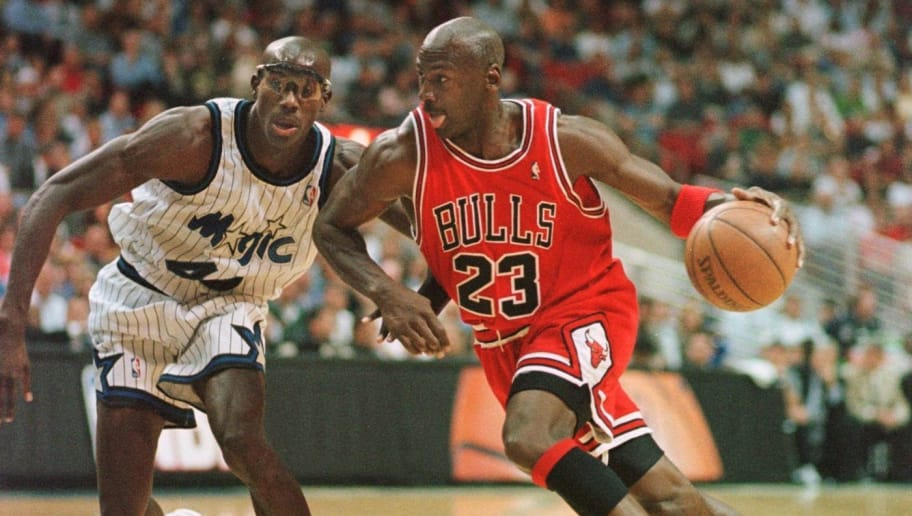 ORLANDO, UNITED STATES:  Chicago Bulls guard Michael Jordan drives past Orlando Magic forward Charles Outlaw for two points during the first period of the game at the Arena in Orlando, 25 March. AFP PHOTO TONY RANZE (Photo credit should read TONY RANZE/AFP/Getty Images)