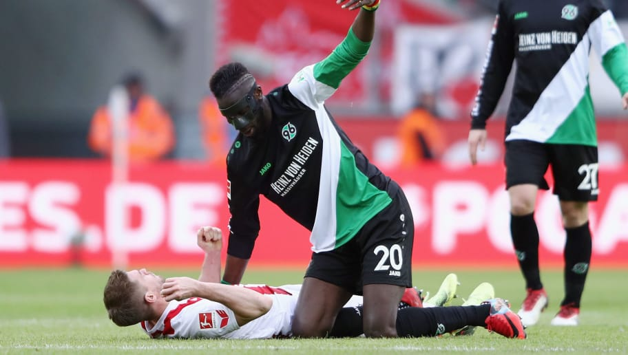 COLOGNE, GERMANY - FEBRUARY 17: Salif Sane of Hannover calls for the Koeln team doctors after hitting Simon Terodde of Koeln during the Bundesliga match between 1. FC Koeln and Hannover 96 at RheinEnergieStadion on February 17, 2018 in Cologne, Germany.  (Photo by Alex Grimm/Bongarts/Getty Images)