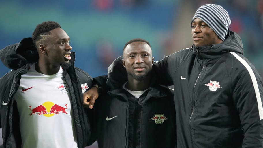 LEIPZIG, GERMANY - JANUARY 13: Naby Keita (C) of Leipzig is hugged by Jean Kevin Augustin (L) and goalkeeper Yvon Mvogo (R) of Leipzig after the Bundesliga match between RB Leipzig and FC Schalke 04 at Red Bull Arena on January 13, 2018 in Leipzig, Germany. (Photo by Ronny Hartmann/Bongarts/Getty Images)