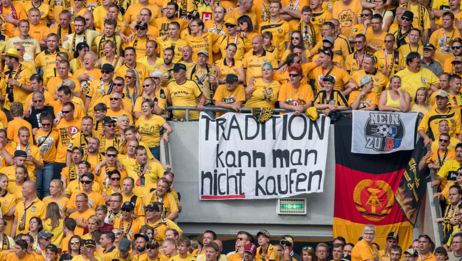Picture taken on August 20, 2016 shows Dresden's fans holding banners reading 'you cannot buy tradition' and 'No to RB' during the German Cup (DFB Pokal) first round football match between SG Dynamo Dresden and RB Leipzig, in Dresden, eastern Germany. Hostility is becoming obvious in Germany against football clubs completely controlled and financed by companies, such as RB Leipzig supported by Red Bull. / AFP / dpa / Thomas Eisenhuth / XGTY - GERMANY OUT  - RESTRICTIONS: ACCORDING TO DFB RULES IMAGE SEQUENCES TO SIMULATE VIDEO IS NOT ALLOWED DURING MATCH TIME. MOBILE (MMS) USE IS NOT ALLOWED DURING AND FOR FURTHER TWO HOURS AFTER THE MATCH. == RESTRICTED TO EDITORIAL USE == FOR MORE INFORMATION CONTACT DFB DIRECTLY AT +49 69 67880   / TO GO WITH AFP STORY by CHRISTOPHE BEAUDUFE         (Photo credit should read THOMAS EISENHUTH/AFP/Getty Images)